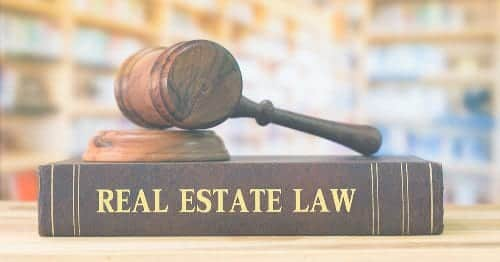 A brown book with Real Estate Law lettering with gavel atop for Texas Property Deeds